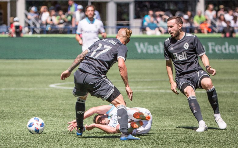 Seattle Sounder's Nicolas Lodeiro falls to the ground trying to get the ball from Vancouver's Marcel de Jong during the game at CenturyLink Field on Saturday. (Rebekah Welch / The Seattle Times)
