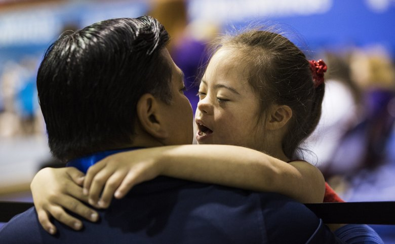 Eight-year-old Frannie Ronan, the youngest competitor at the 2018 Special Olympics gymnastics, embraces her father, Mike, before competing on the balance beam at Royal Brougham Pavilion on Tuesday, July 3, 2018.  (Rebekah Welch / The Seattle Times)