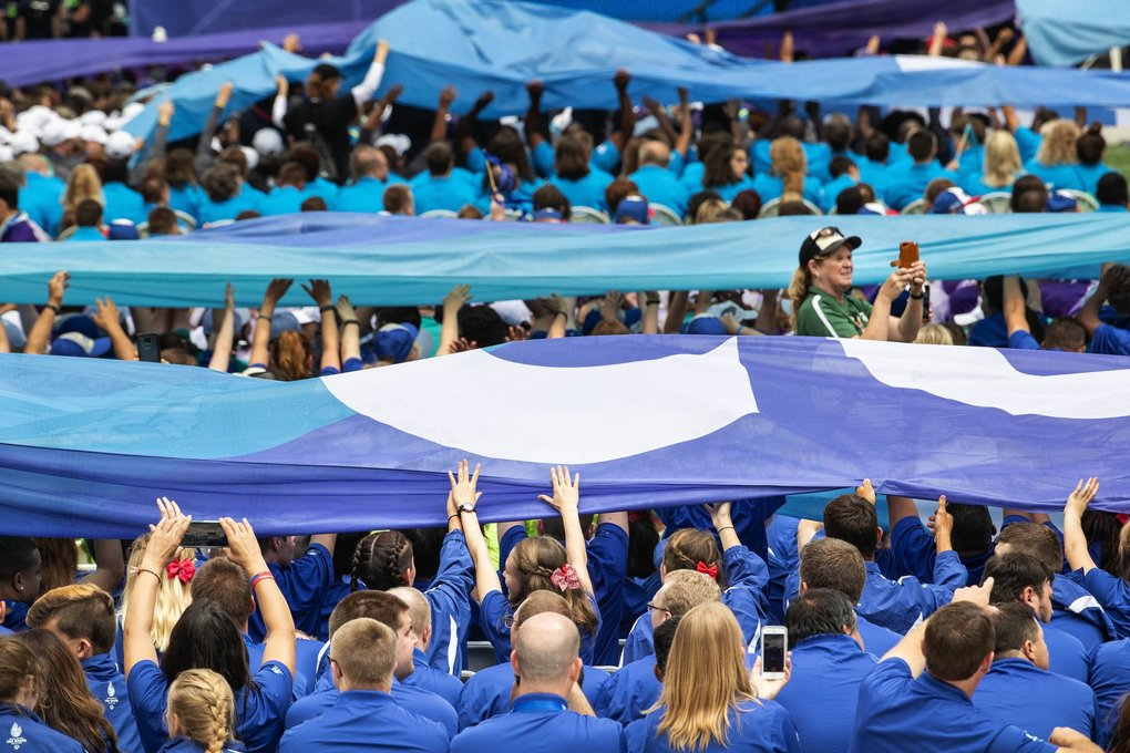 Athletes help move ribbons of words promoting courage and values over their heads during Opening Ceremonies. (Dean Rutz / The Seattle Times)