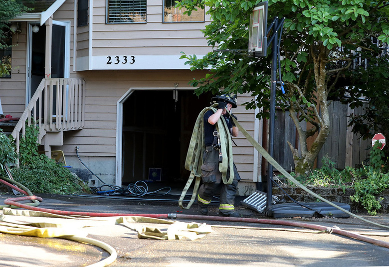 A Seattle firefighter gathers hoses in the aftermath of a house fire at on Northeast 94th Street in North Seattle on Wednesday. (Greg Gilbert/ The Seattle Times)
