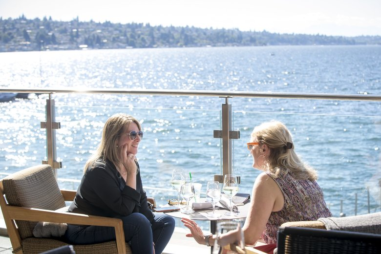 Tanya Perry, left, and Cindy Hartner chat over wine at Water's Table, a restaurant with a patio that overlooks the water at the Hyatt Regency Lake Washington in Renton. (Bettina Hansen/The Seattle Times)