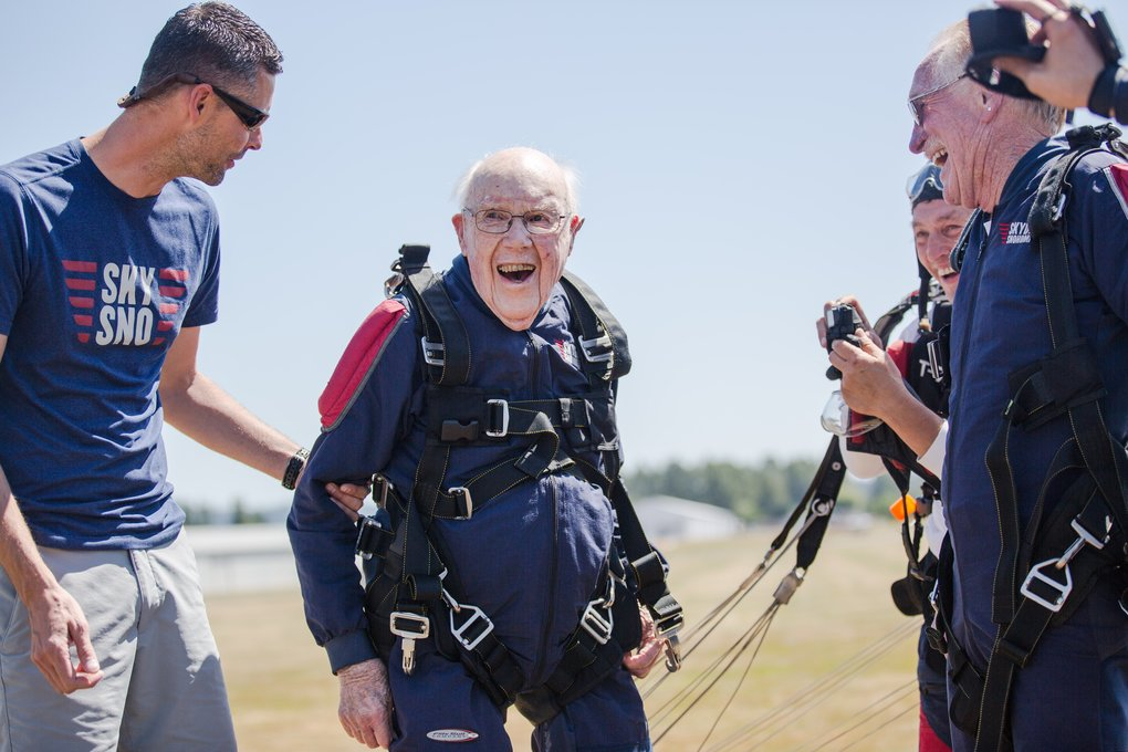 "Robert ""Stu"" Williamson grins after making a smooth landing at Skydive Snohomish. Williamson's longtime friend Tom Carpenter, right, came from Alabama to help celebrate Williamson's 100th birthday. (Rebekah Welch/The Seattle Times)"
