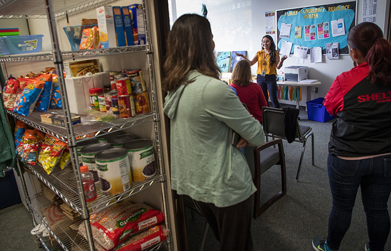 Esmy Farias, family-community resource center coordinator for Vancouver Public Schools at Discovery Middle School, talks to a group of visiting educators from around the northwest interested in the FCRC program. At left is a pantry and supplies for students in need.  In Vancouver Washington, between 2005 and 2015, student poverty rates in their public schools rose from just about a third to more than 50 percent. The district responded by creating new family-community resource centers, which serve as a safe and secure space for students whose families struggle to provide basic needs like food, medical care and stable housing. FCRC coordinators now work at 18 schools where poverty is most concentrated in the district and connect those families to the agencies and services they need so students and teachers can focus on learning in the classroom.  Photographed on May 10, 2018