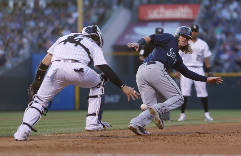 Colorado Rockies catcher Tony Wolters, front, drops the ball as he pursues Seattle's Ben Gamel in a rundown between first and second bases in the fourth inning. Gamel was eventually tagged out on the play. (Mark J. Terrill/The Associated Press)