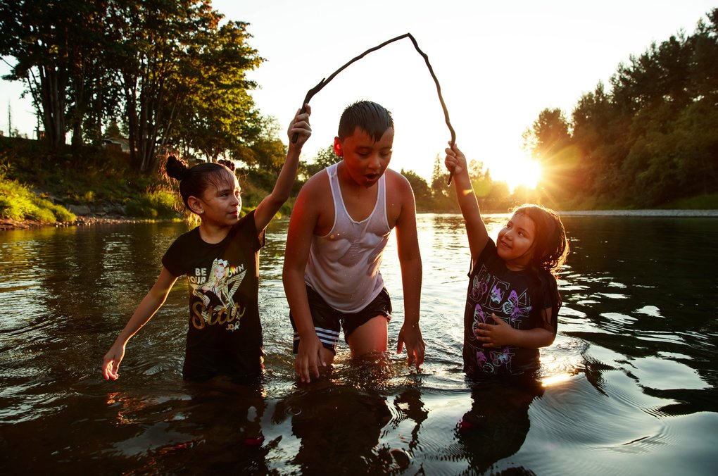 Angie Arroyo, 8, left, Emiliano Vazquez, 10, and Victoria Arroyo, 5, play in the Snoqualmie River near Fall City on Tuesday. The Arroyo sisters were visiting from California, and their families spent the evening by the river to keep cool. The National Weather Service predicts hot, dry weather with highs in the 80s and low 90s through the weekend.  (Erika Schultz/The Seattle Times)