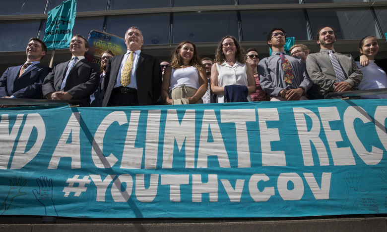 FILE – In this July 18, 2018, file photo, lawyers and youth plaintiffs lineup behind a banner after a hearing before Federal District Court Judge Ann Aiken between lawyers for the Trump Administration and the so called Climate Kids in Federal Court in Eugene, Ore. The lawsuit filed by young activists who say the government is failing to protect them from climate change is still alive. In San Francisco on Friday, July 20, 2018, the 9th U.S. Circuit Court of Appeals rejected the government's second request for an order directing a lower court to dismiss the case. (Chris Pietsch/The Register-Guard via AP, File)
