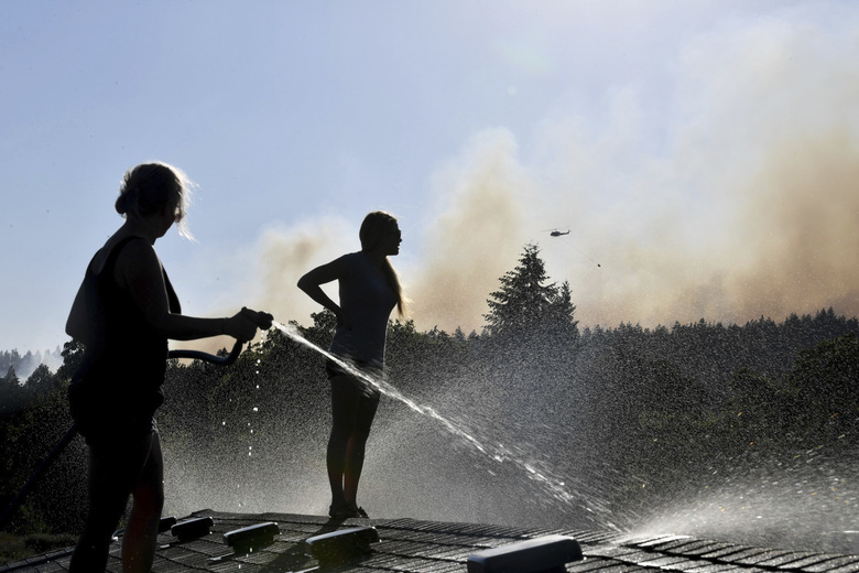 In this Tuesday, July 17, 2018 photo, Deidre Mallgren, left, hoses down the roof of her friend at right, Lindsey Bennett's home as helicopters attack a fast moving wildfire, in Spokane Valley, Wash. (Tyler Tjomsland /The Spokesman-Review via AP)