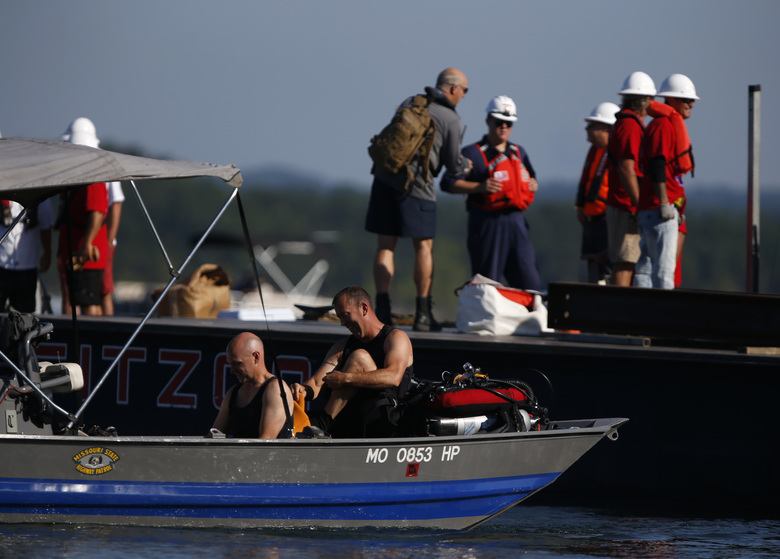 Using a barge mounted crane, a salvage crew from Fitzco Marine Group begin the process of raising a duck boat from below the surface of Table Rock Lake on Monday, July 23, 2018. 17 people were killed last week when the duck boat sank. (Nathan Papes /The Springfield News-Leader via AP)