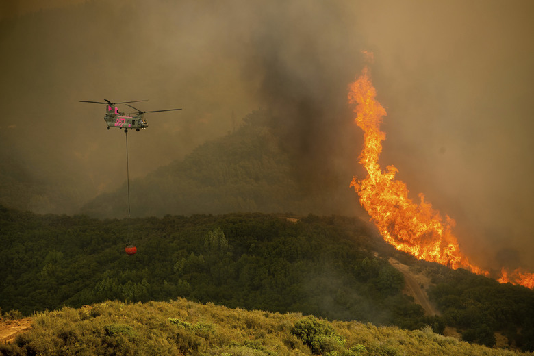 A helicopter carries water while battling the River Fire burning in Lakeport, Calif., Tuesday, July 31, 2018. Firefighters pressed their battle against a pair of fires across Mendocino and Lake counties. In all, roughly 19,000 people have been warned to flee and 10,000 homes remain under threat. (AP Photo/Noah Berger)