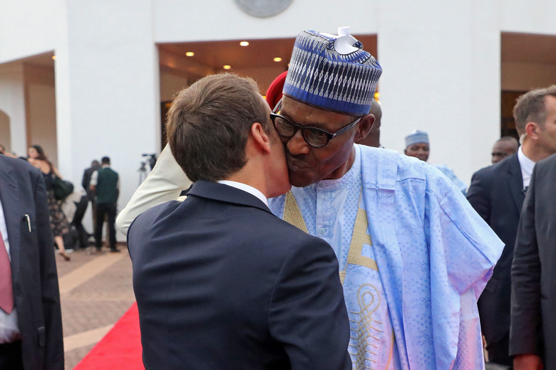 In this picture taken on Tuesday, July 3, 2018 Nigeria's President Muhammadu Buhari, right, embraces his French counterpart, Emmanuel Macron, after a joint press conference held at the Presidential State House, in Abuja, Nigeria. Macron has arrived in Abuja for a meeting with his Nigerian counterpart Muhammadu Buhari, in his latest attempt to forge closer ties with English-speaking Africa. (Ludovic Marin/Pool Photo via AP)