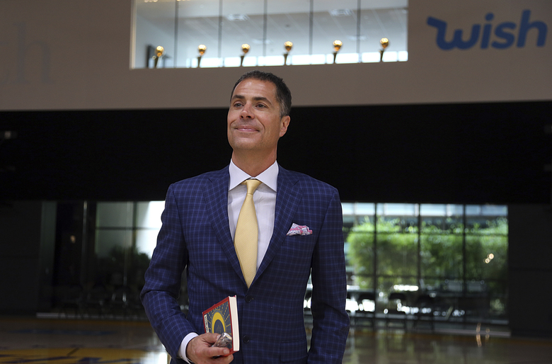 "Los Angeles Lakers general manager Rob Pelinka waits to speak about the acquisition of LeBron James and other free agents at a news conference, with Lakers championship trophies visible in a window, above, at the NBA basketball team's headquarters in El Segundo, Calif., Wednesday, July 11, 2018. He's holding a copy of ""The Alchemist"" by Paolo Coelho, from which he read a passage. (AP Photo/Reed Saxon)"