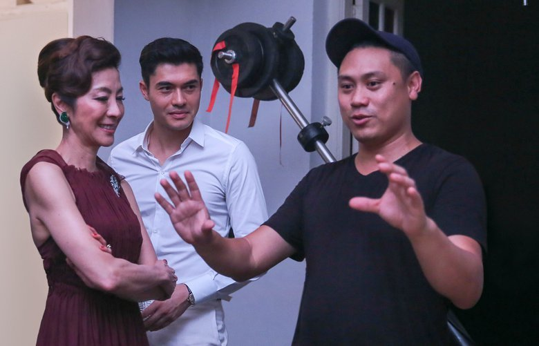 Michelle Yeoh, Henry Golding, center, and director Jon M. Chu on the set of ?Crazy Rich Asians.?