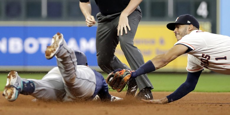 Houston Astros shortstop Carlos Correa (1) dives to tag Seattle Mariners' Ryon Healy during the fourth inning of a baseball game Saturday in Houston. Healy was out at second while trying to stretch a single into a double.  (David J. Phillip / The Associated Press)