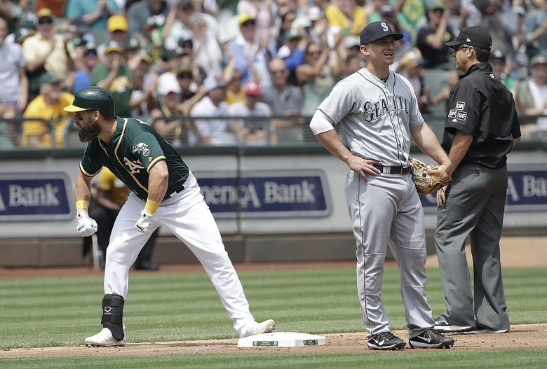 Oakland Athletics' Nick Martini, left, reacts after hitting a triple next to Seattle Mariners third baseman Kyle Seager during the fourth inning of a baseball game in Oakland, Calif., Wednesday, Aug. 15, 2018. (Jeff Chiu / The Associated Press)