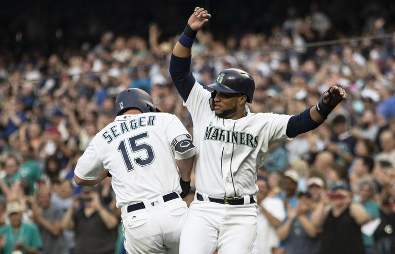 Seattle Mariners' Kyle Seager (15), Robinson Cano, right, and Nelson Cruz celebrate after Seager hit a three-run home run off Los Angeles Dodgers starting pitcher Rich Hill during the first inning of a baseball game Saturday, Aug. 18, 2018, in Seattle. (AP Photo/Stephen Brashear) WASB106 WASB106