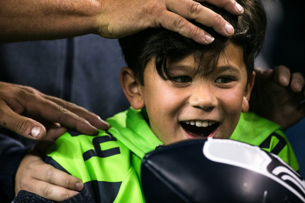 A young Seahawks fan grins after after getting an autograph from a player after Seahawks battled the Raiders at CenturyLink Field, Thursday. (Rebekah Welch / The Seattle Times)