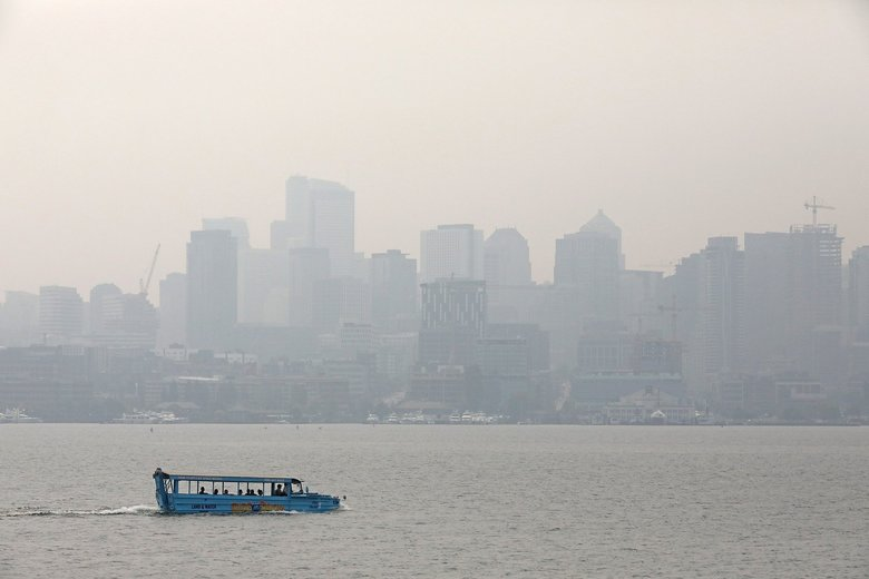 A duck boat takes tourists around Lake Union on a hazy day in August. Business owners and community leaders in Washington state's outdoors industry reported drops in business during this summer's smoky days. (Greg Gilbert / The Seattle Times)