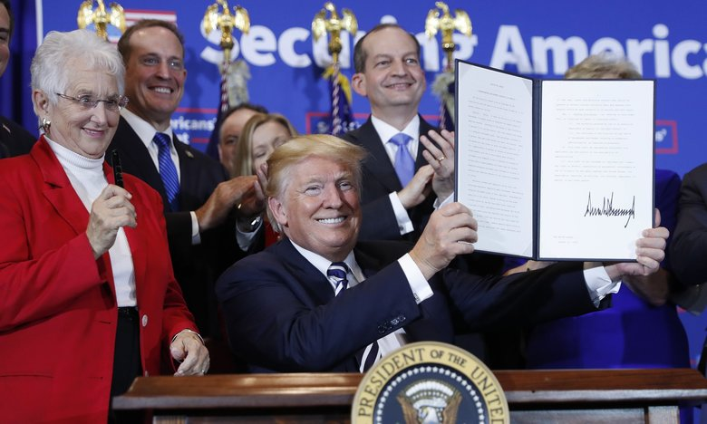 President Donald Trump holds up a signed executive order on stage at the Harris Conference Center in Charlotte, NC., Friday, Aug. 31, 2018. The executive order aims to make it easier for small businesses to group together to provide their workers with retirement plans. On the left is Rep. Virginia Foxx, R-NC. (Pablo Martinez Monsivais / The Associated Press)