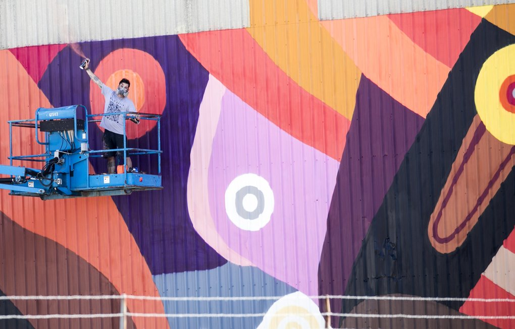 Brazilian artist Fernando Chamarelli gives a spray-paint salute while working on his piece along the SODO Track. (Bettina Hansen/The Seattle Times)