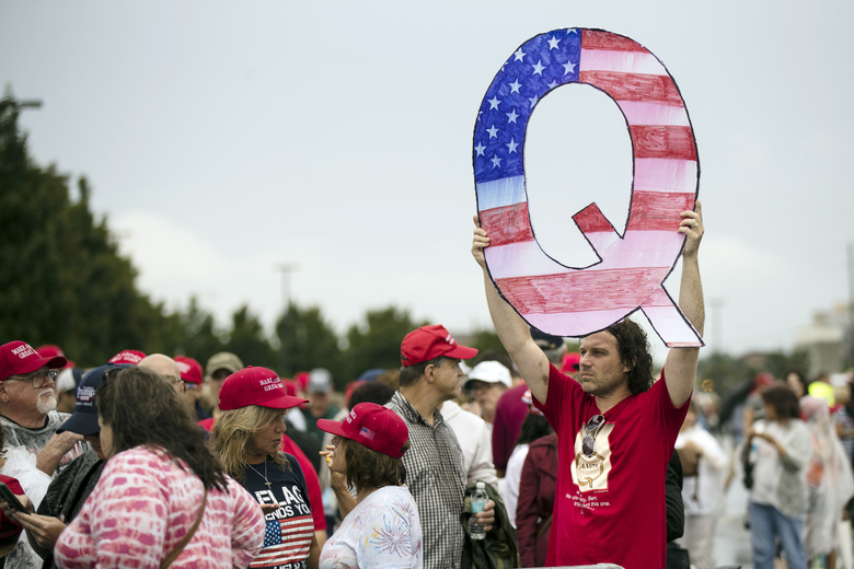 David Reinert holding a Q sign waits in line to enter a campaign rally with President Donald Trump Thursday in Wilkes-Barre, Pa. (AP Photo/Matt Rourke)