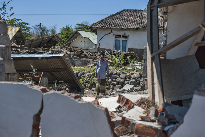 A man inspects a village destroyed by a strong earthquake in Kayangan, Lombok Island, Indonesia, Monday, Aug. 6, 2018. Indonesian authorities said Monday that rescuers still haven't reached some devastated parts of the tourist island of Lombok after the powerful earthquake flattened houses and toppled bridges, killing large number of people and shaking neighboring Bali. (AP Photo/Fauzy Chaniago)