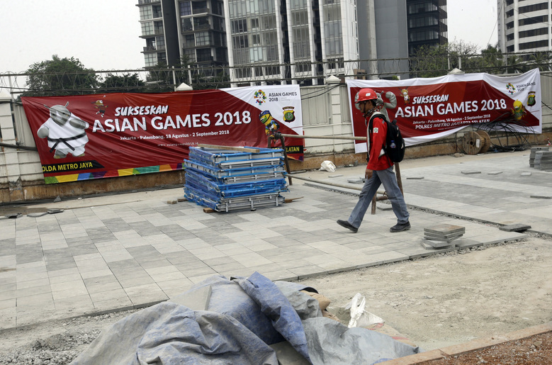 In this July 26, 2018 photo, a worker walks on the sidewalk which is being renovated ahead of the 2018 Asian Games at the main business district in Jakarta, Indonesia. The country is deploying 100,000 police and soldiers to provide security for the Asian Games, the biggest event ever held in its terror attack prone capital Jakarta, parts of which have been dramatically spruced up as the city readies to welcome tens of thousands of athletes and visitors. (AP Photo/Tatan Syuflana)