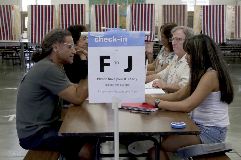 Robert Quartero, 50, left, of Honolulu, sits at a table at a polling place during Hawaii's primary election, Saturday, Aug. 11, 2018 in Honolulu. The winners of most of the Democratic Party's primary races in Hawaii this weekend will be the favorites to win the general election in November. The most hotly contested matches in this deep blue state on Saturday are for governor and the state's 1st Congressional District. (AP Photo/Caleb Jones)