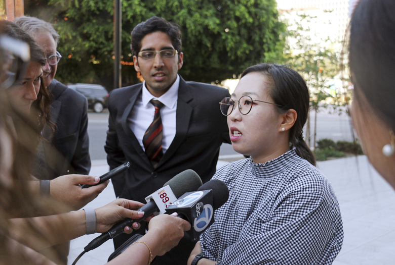 Yea Ji Sea, a former U.S. Army specialist who was born in South Korea, and her attorney Sameer Ahmed talk with reporters after a federal court hearing in Los Angeles Tuesday, Aug. 14, 2018. Sea filed a lawsuit in July, 2018, demanding a response to her citizenship application after the military moved to discharge her. She has since been discharged. U.S. District Judge Michael Fitzgerald says the government will have to rule on Sea's application by Sept. 5 or explain the delay to the court. (AP Photo/Ariel Tu)