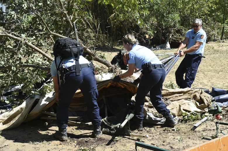 In this photo provided by the French Gendarmerie Nationale, gendarmes remove a tent after floods at Saint-Julien de Peyrolas camping site, in southern France, Friday, Aug. 10, 2018. About 1,600 people have been evacuated due to flash flooding in southern France, most of them from campsites near swollen rivers and streams. (Jose Rocha/French Gendarmerie Nationale via AP)