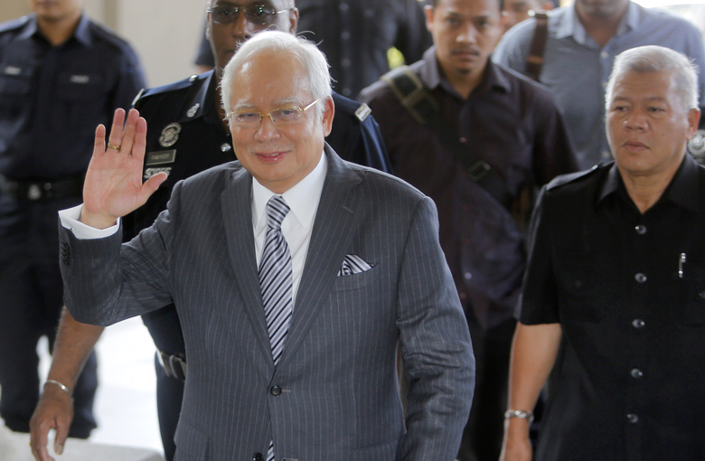 Malaysian former Prime Minister Najib Razak waves to the media as he walks in High Court of Malaya in Kuala Lumpur, Malaysia, Friday, Aug. 10, 2018. Najib was charged of money laundering on Wednesday over a multibillion-dollar graft scandal at a state investment fund, the anti-corruption agency said. (AP Photo/Yam G-Jun)