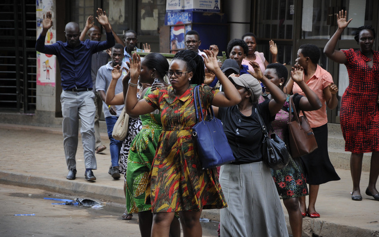 Residents are ordered out of a building with their hands in the air as security forces pursue protesters in Kampala, Uganda, Monday, Aug. 20, 2018. Ugandan police fired bullets and tear gas to disperse a crowd of protesters demanding the release of jailed lawmaker, pop star, and government critic Kyagulanyi Ssentamu, whose stage name is Bobi Wine. (AP Photo/Ronald Kabuubi)
