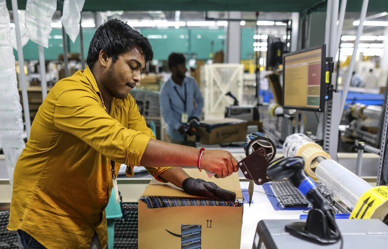 An employee prepares a package for shipment at the Amazon.com Inc. fulfillment center in Hyderabad, India on Thursday, Sept. 7, 2017. Amazon opened its largest Indian fulfillment center in Hyderabad. The center spans 400,000 square feet with 2.1m cubic feet of storage capacity the company said in a statement. Photographer: Dhiraj Singh/Bloomberg 775039070