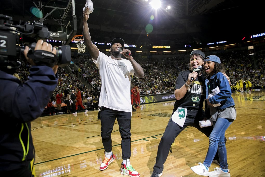 Basketball star Nate Robinson, along with Storm emcee Shellie Hart and his daughter Navyi Caiann Robinson, hype up the crowd during game one of the WNBA Finals as the Seattle Storm take on the Washington Mystics at KeyArena in Seattle Friday, September 7, 2018. (Bettina Hansen / The Seattle Times)