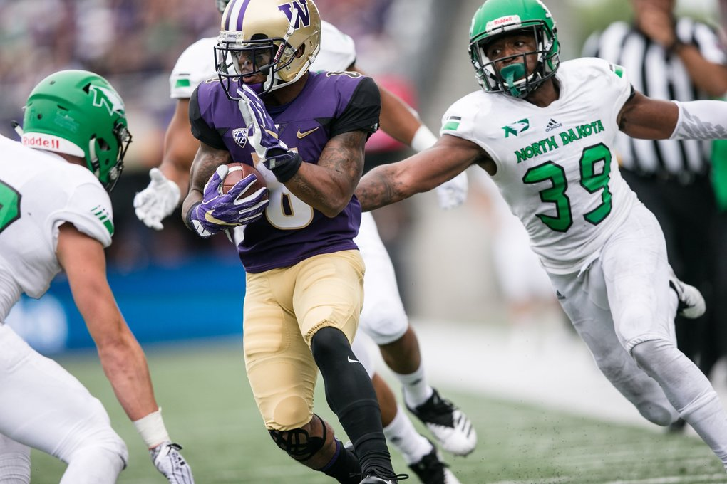 Wide Receiver Chico McClatcher completes a pass and pushes far down the field, avoiding a tackle from Defensive Back Tykeise Johnson as the Huskies battle the North Dakota Fighting Hawks at Husky Stadium on Saturday, September 8. (Rebekah Welch / The Seattle Times)
