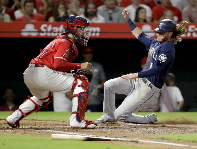 Ben Gamel scores past Angels catcher Jefry Marte on a sacrifice fly by Dee Gordon during the second inning Thursday. (Chris Carlson / The Associated Press)