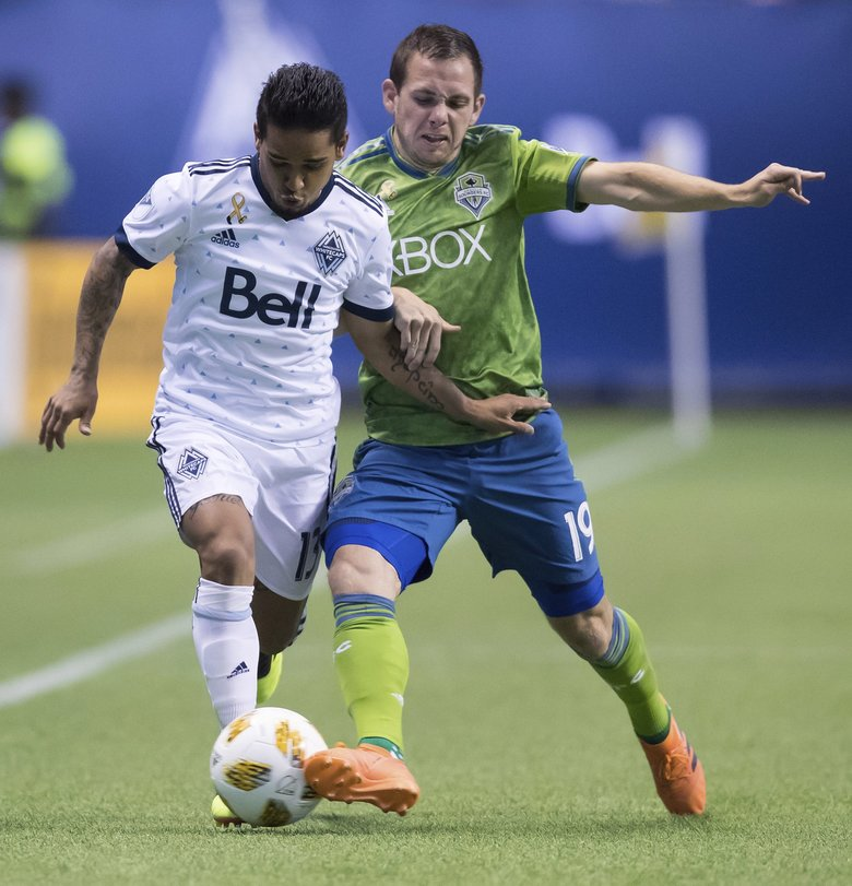 Seattle Sounders' Harry Shipp (19) kicks the ball away from Vancouver Whitecaps' Cristian Techera (13) during the first half of an MLS soccer match, Saturday, Sept. 15, 2018, in Vancouver, British Columbia. (Darryl Dyck/The Canadian Press via AP) VCRD202 VCRD202 (Darryl Dyck / The Associated Press)