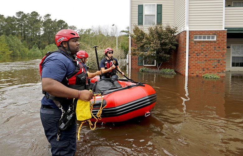 People are rescued Monday from a flooded neighborhood in Spring Lake, N.C. (AP Photo/David Goldman)