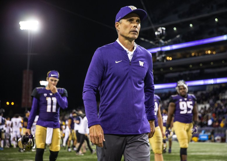 Chris Petersen walks off with his Huskies following a 27-20 win over Arizona State. (Dean Rutz / The Seattle Times)