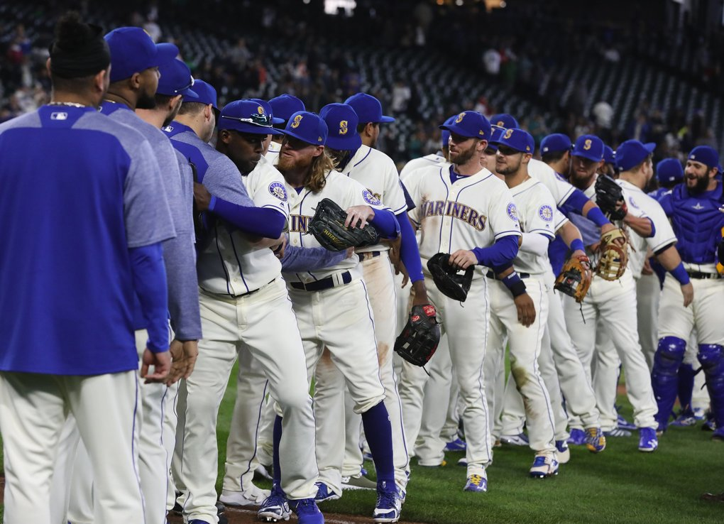 Mariners embrace each other after defeating Texas at the final game of the season Sunday, Sept. 30, 2018, in Seattle. (Ken Lambert / The Seattle Times)