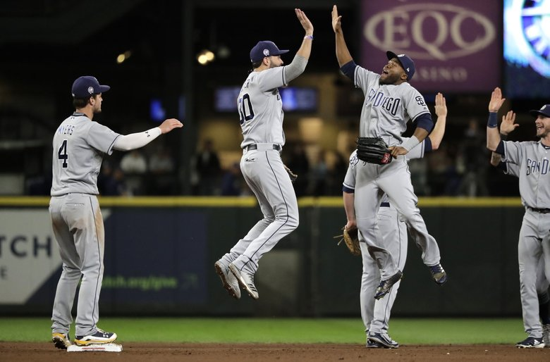 San Diego Padres' Wil Myers, left, looks on as Eric Hosmer, second from left, and Manuel Margot, third from left, celebrate after the Padres beat the Mariners 2-1 in a baseball game, Tuesday, Sept. 11, 2018, in Seattle.  (Ted S. Warren / The Associated Press)