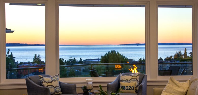 "The living room overlooks the back deck, with view-maximizing glass all around. ""Carl was able to design the house with water views from all the living areas and bedrooms,"" says homeowner Beth Sanger. ""We do not take it for granted."" (Mike Siegel/The Seattle Times)"