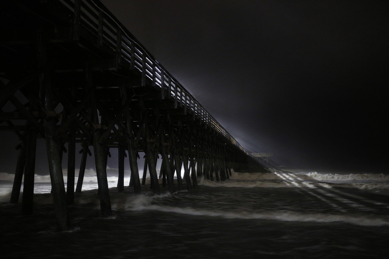 Waves crash on the Second Avenue pier during Hurricane Florence in Myrtle Beach, S.C., Sept. 14, 2018. Florence, which was downgraded to a tropical storm on Friday, was pounding the Carolinas with as much as three inches of rain per hour as it trudged inland; at least five deaths have been reported. (Luke Sharrett/The New York Times)