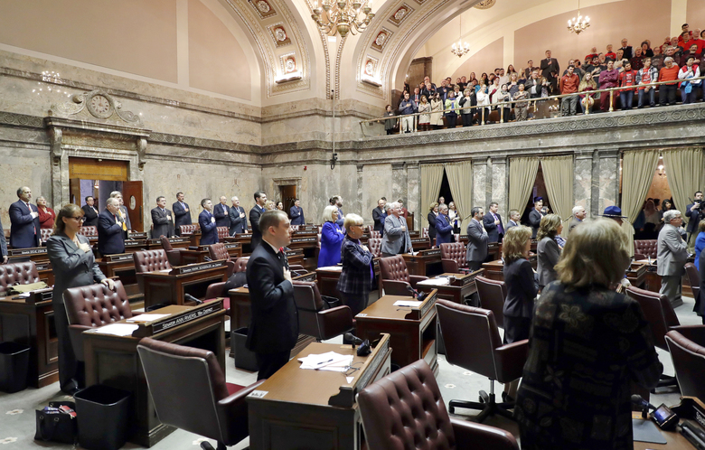 "FILE – In this Jan. 8, 2018 file photo, Washington State senators stand during the ""Pledge of Allegiance"" on the first day of the 2018 legislative session at the Capitol in Olympia, Wash. A public records task force created after Washington lawmakers attempted to exempt themselves from the state's Public Records Act is set to convene its first of four meetings. The inaugural meeting Wednesday, Sept. 5, 2018 will address the topic that caused tension between the Legislature and a coalition of media groups that sued last year: the issue of legislative records and lawmakers' assertion that they are not subject to the same disclosure rules that apply to other elected officials. (AP Photo/Ted S. Warren, File)"