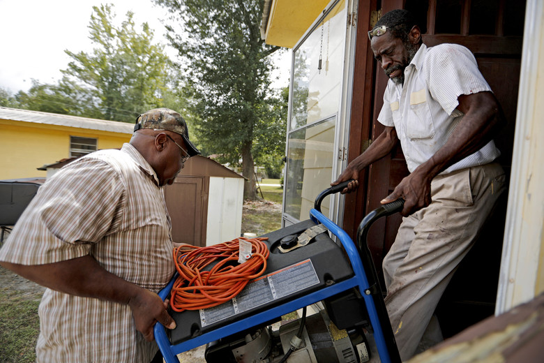 "Thomas Lee, left, gets help from Stoney Williamson, right, lifting a generator into his home which flooded two years ago from Hurricane Matthew in Nichols, S.C., Thursday, Sept. 13, 2018. Few places in South Carolina are more worried about the possibility of disastrous inland flooding from Hurricane Florence's heavy rain than the town of Nichols. ""If it floods like this again, you can just tell Nichols goodbye,"" Lee said. (AP Photo/David Goldman)"