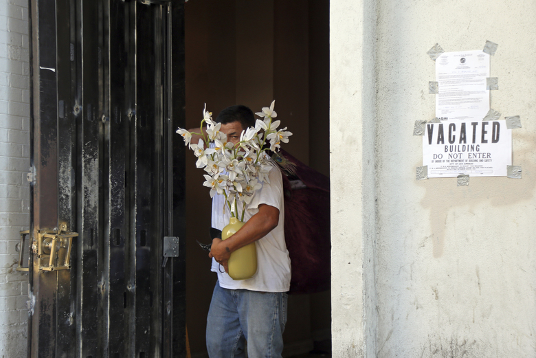 A man carries out a plant for someone who may have been an occupant of a four-story vacant commercial building in Los Angeles' Hollywood district that was raided early in the morning of Wednesday, Sept. 12, 2018. Los Angeles police say more than 60 adults and at least four juveniles were detained during the raid where some people had been squatting. A search warrant was served before dawn on Hollywood Boulevard and officers went through the building, room by room, over several hours. Two firearms — a shotgun and a rifle— and drugs were seized, officials said. (AP Photo/Reed Saxon)