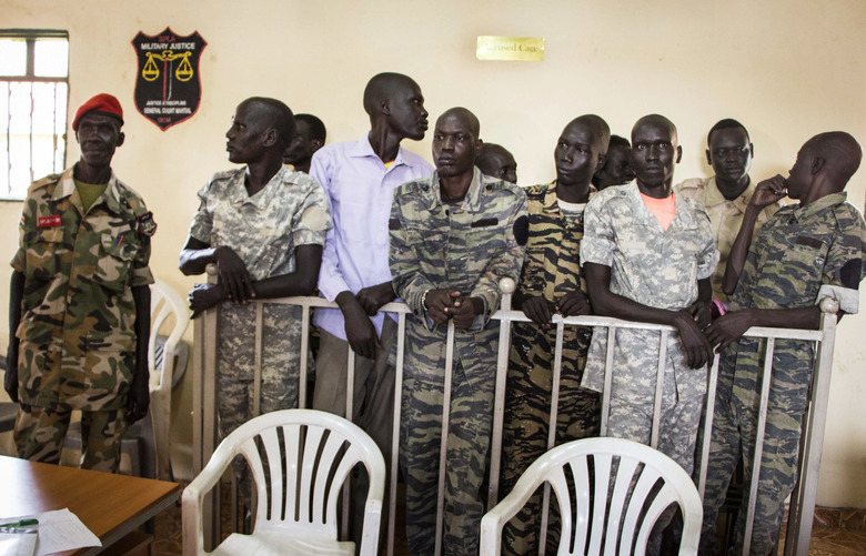 South Sudanese soldiers listen to the verdict being delivered at their trial in a military courtroom in Juba, South Sudan Thursday, Sept. 6, 2018. A military judge found 10 soldiers guilty of rape and murder in a violent rampage at the Terrain Hotel in Juba in 2016, when dozens of soldiers broke into the compound, killed a local journalist and gang-raped five international aid workers. (AP Photo)