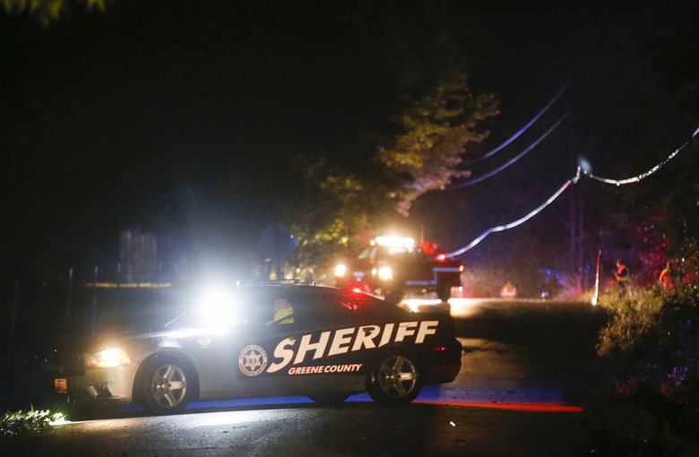 In this Friday, Sept. 7, 2018 photo, crews search for a Greene County Sheriff's deputy believed to have been swept away by high water in northern Greene County, in Mo. The Springfield News-Leader reports that 35-year-old Greene County Deputy Aaron Paul Roberts had just returned to service following a 911 hang-up call Friday night when he radioed that his car had been washed off the road into the Pomme de Terre River in Fair Grove, Mo. Sheriff Jim Arnott says Roberts' body was found inside the car a short time later. (Andrew Jansen/The Springfield News-Leader via AP)