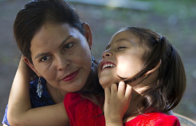 """Araceli Ramos holds her 5-year-old daughter, Alexa, on her lap during an interview in a park in San Miguel, El Salvador, on Aug. 18, 2018. The federal government offers all deported parents the chance totake their children with them, but Ramos said she wasorderedto sign a waiver to leave Alexabehind. """"The agent put his hand on mine, he held my hand, he forced me to sign,"""" she said.(AP Photo/Rebecca Blackwell) NY982 NY982"""