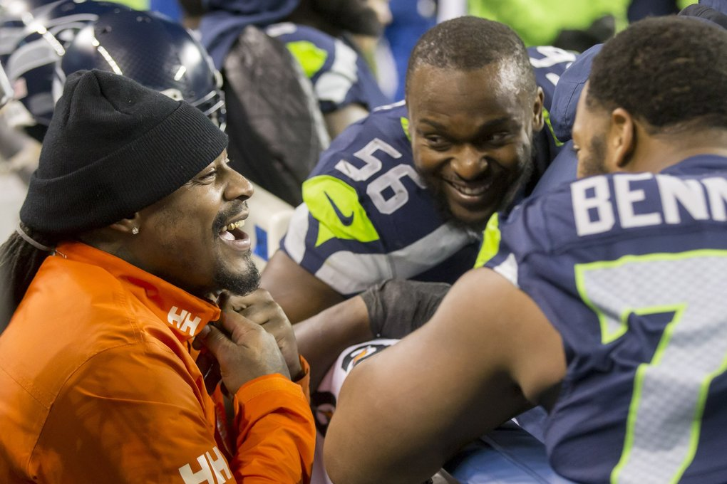Retired running back Marshawn Lynch talks to former teammates defensive end Cliff Avril and defensive end Michael Bennett on the sidelines as the Seattle Seahawks take on the Carolina Panthers, Sunday December 4, 2016 at CenturyLink Field in Seattle.  (Bettina Hansen / The Seattle Times)