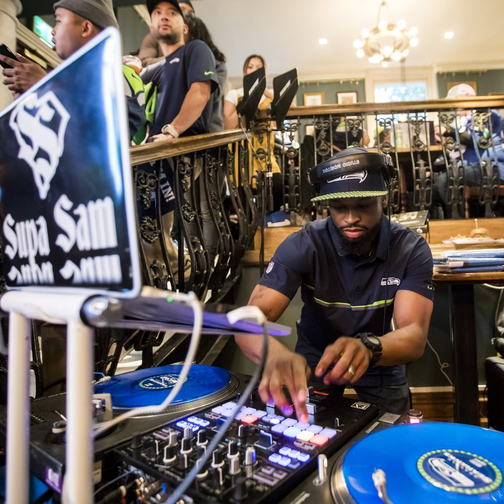 The official DJ of the Seahawks, DJ Supa Sam, spins as fans rally at The Barrowboy and Banker pub, Friday October 12, 2018 prior to Seattle's game against the Oakland Raiders at Wembley on Sunday. (Bettina Hansen / The Seattle Times)